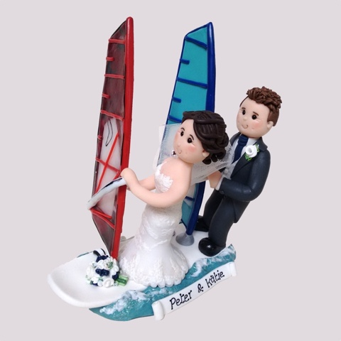 Wedding cake topper of couple on windsurfing boards