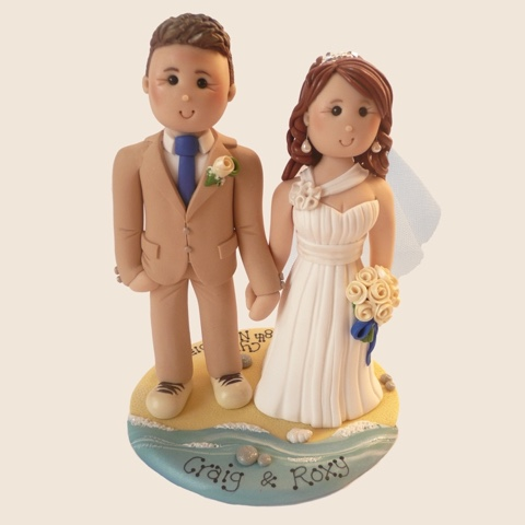 Wedding cake topper of couple on beach