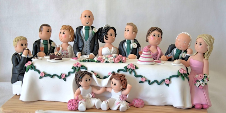 Hand made clay wedding cake topper of head table at wedding.