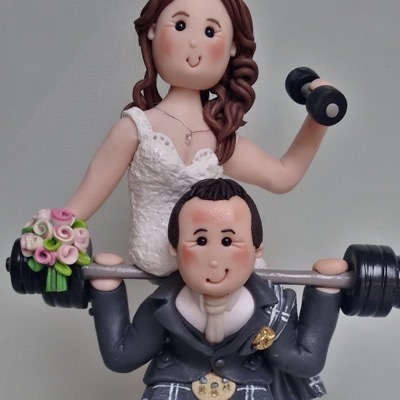 Wedding cake topper with weightlifting couple