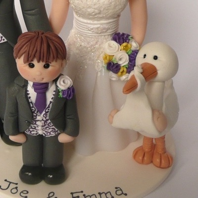 Wedding cake topper with couple with baby delivered by stork