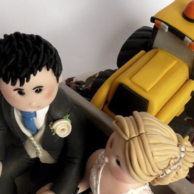 Wedding cake topper with couple sat in digger bucket