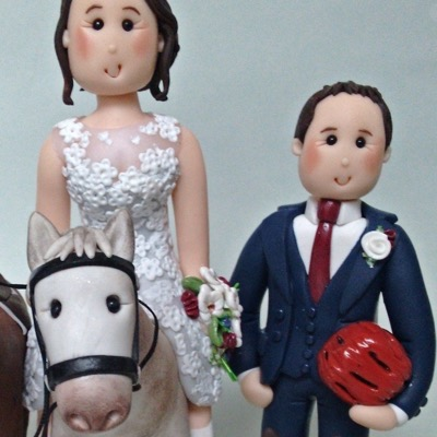 Wedding cake topper of couple with horses and cat