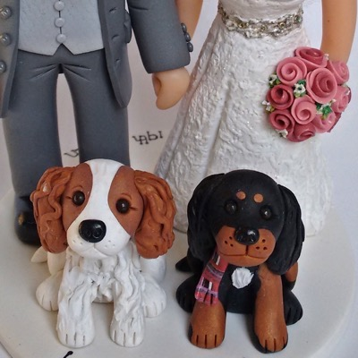 Wedding cake topper of couple with dogs
