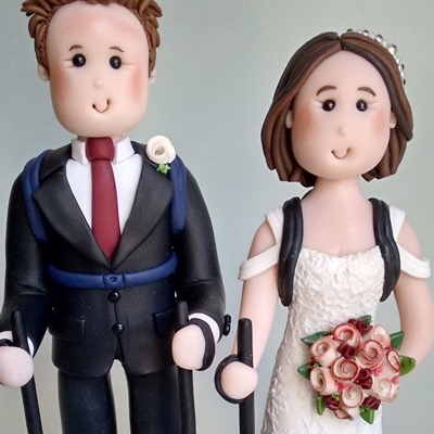 Wedding cake topper of couple on hike