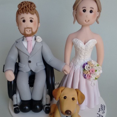 Wedding cake topper of couple with groom in wheelchair