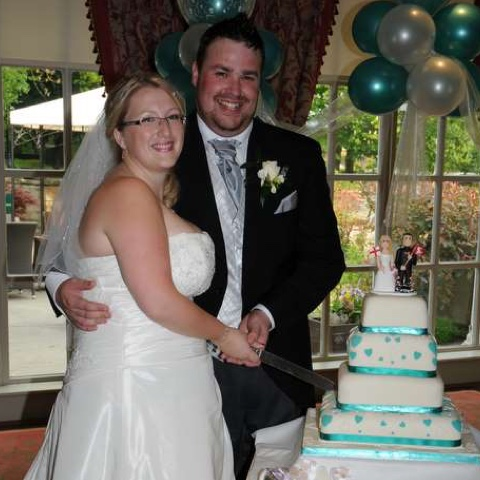 Couple cutting cake with cake topper