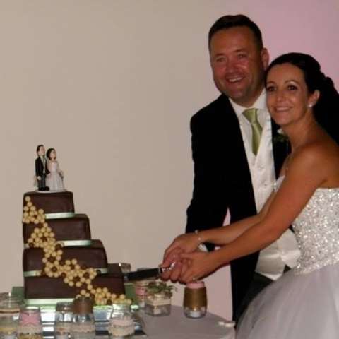 Couple cutting chocolate cake with cake topper