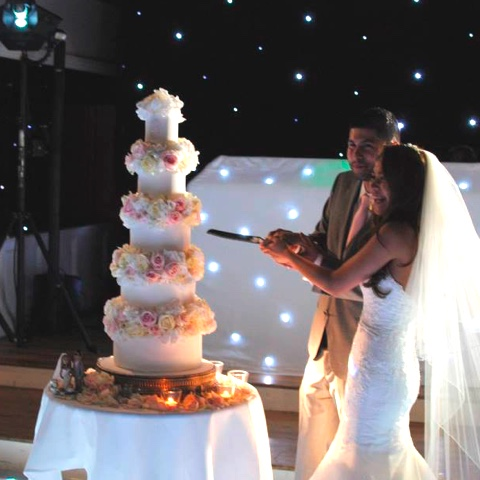 Couple cutting wedding cake with cake topper