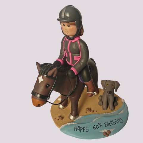 Clay birthday cake topper of person on horse with dog