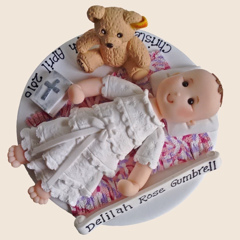 Hand-crafted christening cake topper of baby with teddy-bear