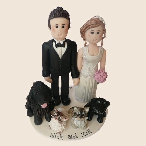 Wedding cake topper of couple with dog and cat pets