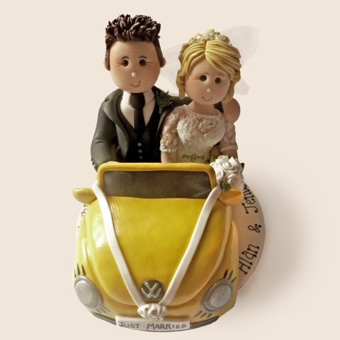 Wedding cake topper of couple in Volkswagen car