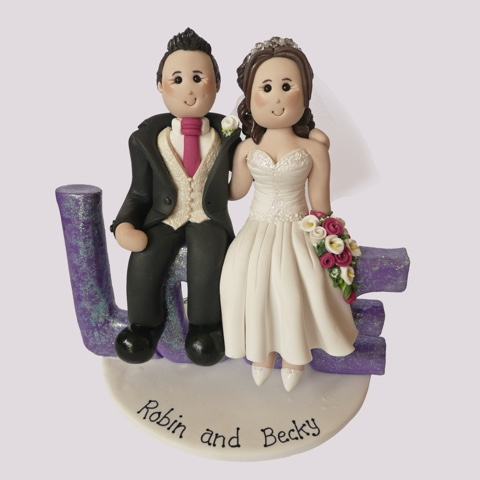 Wedding cake topper of couple sat down