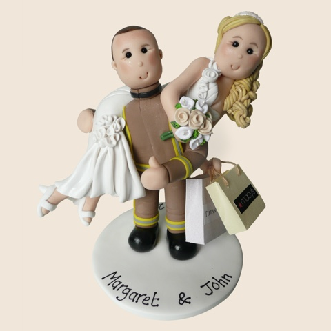 Wedding cake topper with fireman groom lifting bride